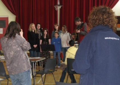the flotta school lasses sing with the trio for the first time, with rebecca marr taking (decent) photos and catherine turnbull (orkney today) looking on